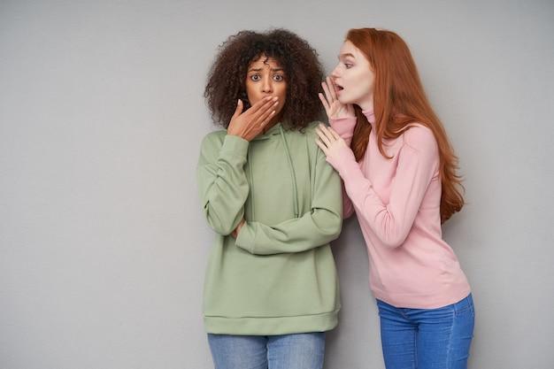 Взволнованная молодая кареглазая кудрявая темнокожая брюнетка прикрыла рот и нахмурила брови, пока ее подруга рассказывала захватывающие новости, стоя у серой стены
