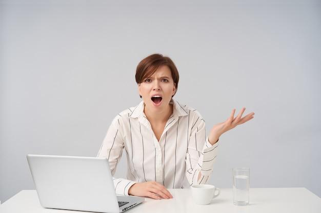 Agitato giovane donna dai capelli castani piuttosto corto con acconciatura casual sollevando emotivamente il palmo con la faccia dispiaciuta, isolato su bianco