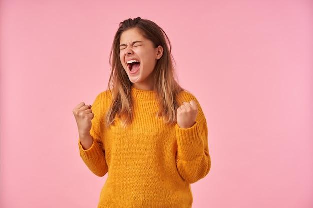 ピンクのマスタードの暖かいセーターを着て、目を閉じて興奮して叫びながら感情的に拳を上げるカジュアルな髪型の興奮した若い茶色の髪の女性