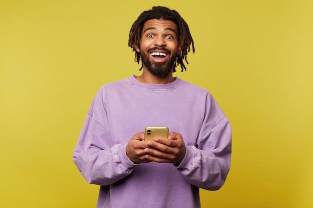 興奮した若いハンサムなブルネットのひげを生やした男性、黒い肌は携帯電話を上げた手で維持し、黄色の背景の上に分離されたカメラを感情的に見ています