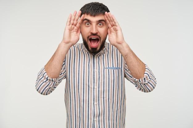 興奮した若いハンサムな黒髪の男性、ひげを生やして目を大きく開いて、白い壁に隔離された彼の顔に手を上げて