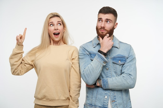 Agitated young lovely blonde woman in beige sweatshirt pointing surprisedly upwards with raised forefinger while posing on white with confused bearded brown haired male
