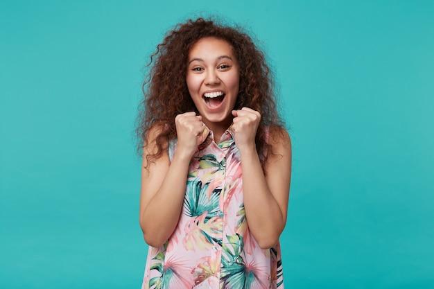 青の上に立って、広い笑顔で興奮して見ながら、カジュアルな髪型で幸せに手を上げて興奮している若い素敵な茶色の髪の巻き毛の女性
