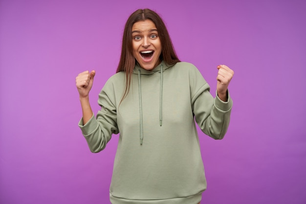 Agitated young lovely brown haired woman dressed in casual clothes raising happily her fists while looking emotionally at front with wide mouth opened, isolated over purple wall