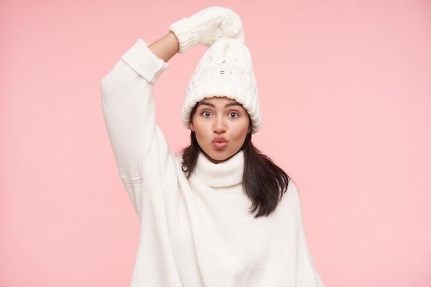 갈색 느슨한 머리를 제기 손으로 그녀의 모자를 당기고 정면에서 흥분을보고, 분홍색 벽 위에 서있는 흥분된 젊은 사랑스러운 갈색 머리 여자