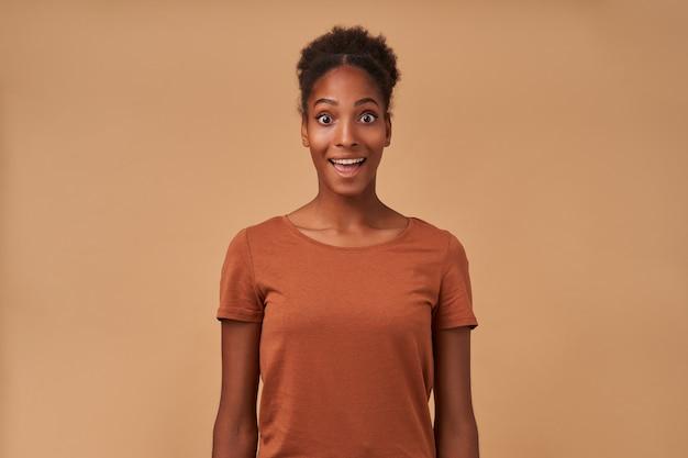 ベージュの上に立って、興奮して見ながら驚くほど眉を上げるお団子の髪型を持つ興奮した若い素敵な巻き毛の暗い肌の女性