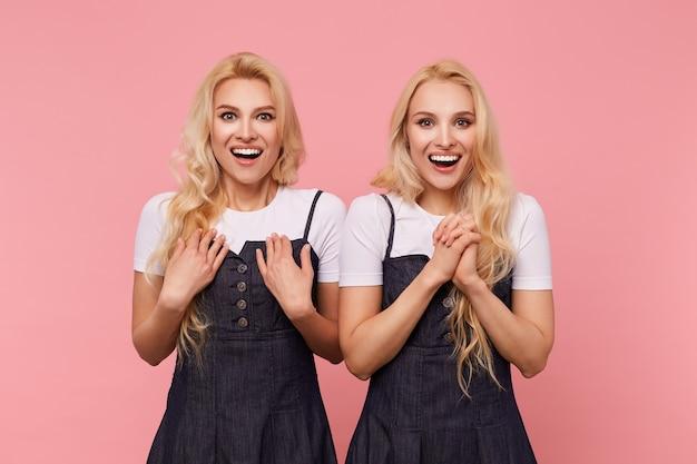 ピンクの背景の上に分離された、カメラを見て、感情的に手を上げている間、元気に笑っている興奮した若い素敵な長い髪のブロンドの女性