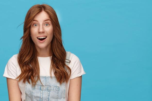 파란색 배경 위에 포즈를 취하는 동안 기본 흰색 티셔츠를 입고 즐거운 미소로 카메라를 흥분하게보고 곱슬 머리를 가진 흥분된 젊은 사랑스러운 빨간 머리 여성