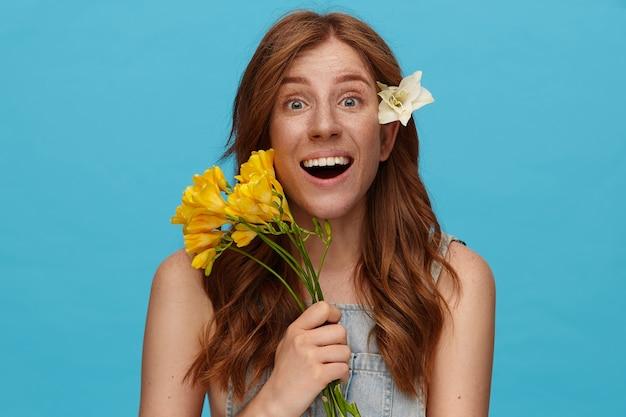 カメラを見ながら興奮して緑の目を丸め、青い背景の上にポーズをとっている間黄色の花を保持している波状の髪型を持つ興奮した若い素敵な赤毛の女性