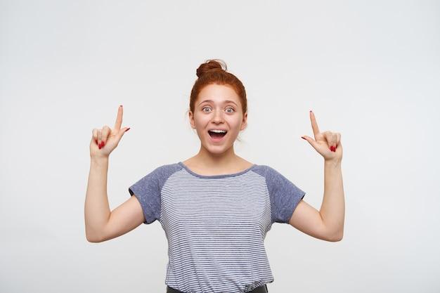 Взволнованная молодая красивая рыжая женщина с непринужденной прической смотрит широко открытыми глазами и ртом, держа указательные пальцы поднятыми, стоя над белой стеной
