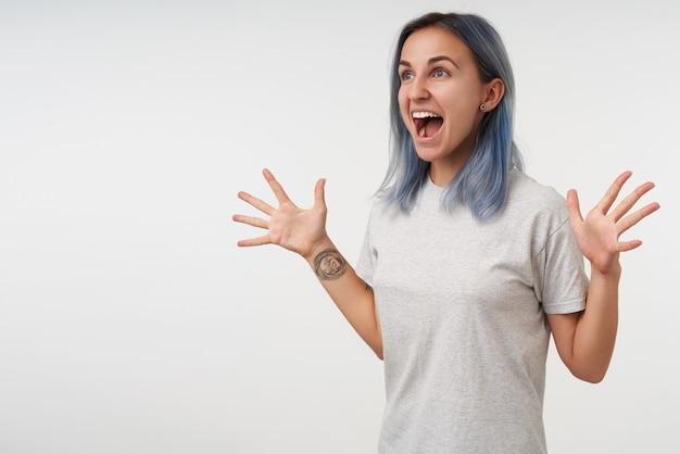 興奮して若い素敵な短い髪の女性は、白で隔離され、広い口を開いて興奮して前方を見ながら手を上げたままのタットを持っています