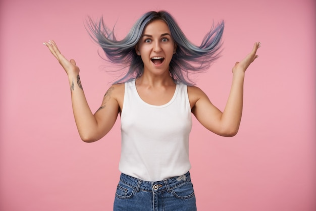 Agitata giovane femmina piuttosto tatuata con capelli blu selvaggi che guarda eccitata con la bocca larga aperta e tenendo le mani alzate mentre posa sul rosa