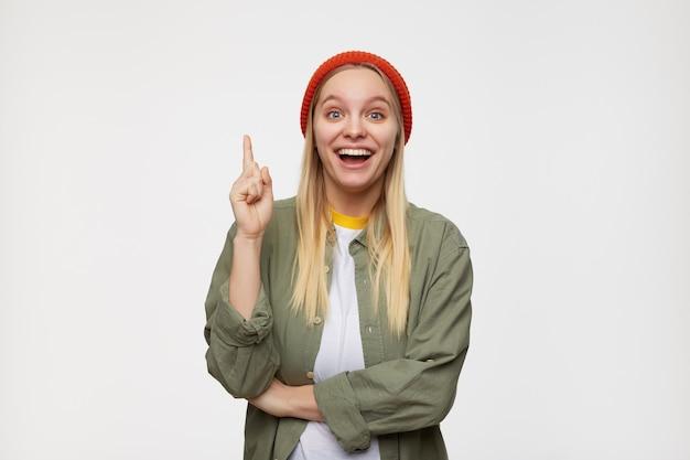 Agitato giovane femmina graziosa dalla testa bianca che alza il dito indice eccitato come se avesse un'idea e guardasse con gioia, in piedi contro il blu