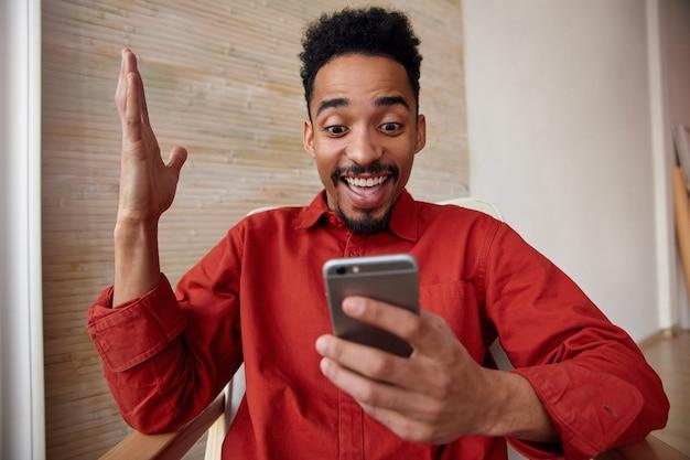 Giovane maschio barbuto dai capelli corti agitato che alza emotivamente la mano e alza le sopracciglia sorprendentemente mentre guarda volentieri sul suo smartphone, in posa su interni beige