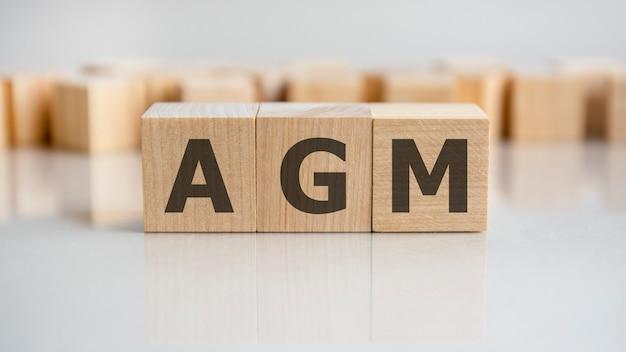 Agm 단어는 회색 테이블에 누워 있는 나무 빌딩 블록으로 만들어집니다.