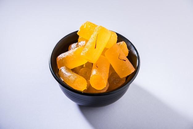 アグラのシャヒペタ-サフランをトッピングした砂糖シロップに浸したカボチャのかけらを使って作られた甘いキャンディーです。不機嫌そうな背景の上にプレートでお召し上がりいただけます。セレクティブフォーカス