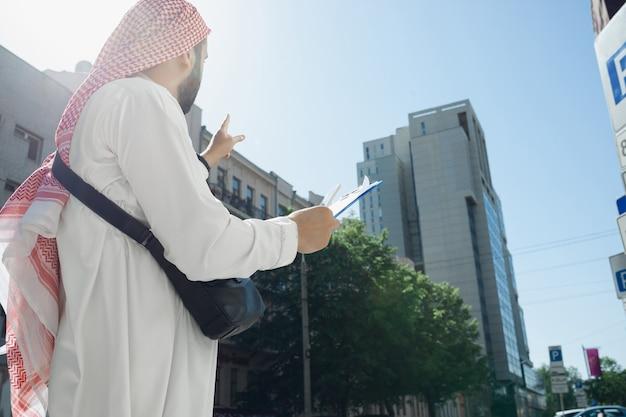 합의. 부동산을 사는 동안 부유한 아라비아 남자의 초상화, 도시의 비즈니스 센터. 민족, 문화. 거래를 성공적으로 만드는 전통 의상을 입은 자신감 있는 남자. 금융, 경제.