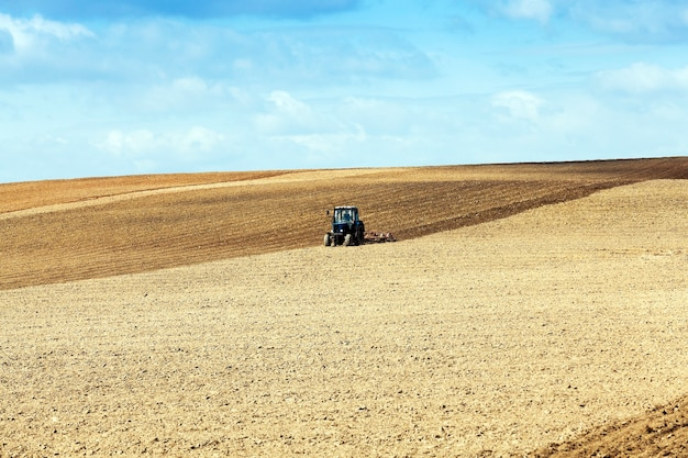 作物を播種するために耕された春のトラクターである農地