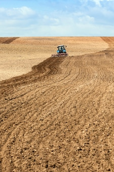 Сельскохозяйственное поле, на котором пашет трактор.