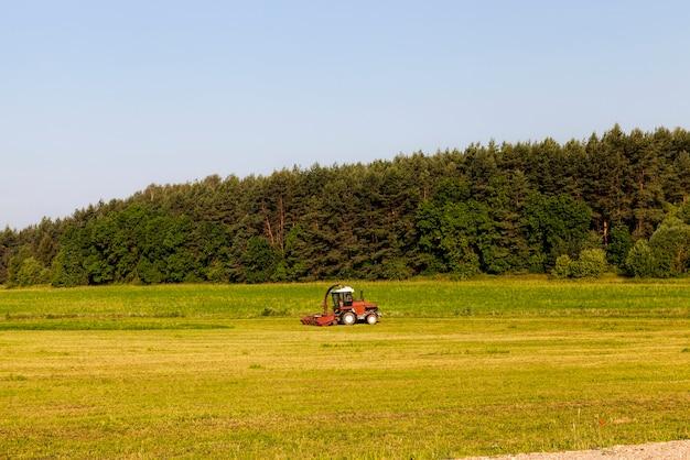 森の近くにトラクターがある農地
