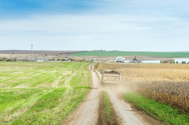 농장으로가는 길을 여행하는 트랙터 트레일러가있는 농업 분야
