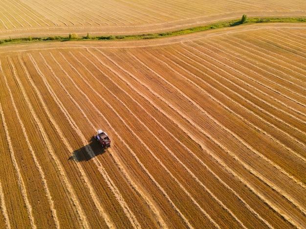 밀의 노란색 필드에 농업 수확기입니다. 다채로운 필드의 공중 무인 항공기 보기입니다. 여름철 밀 수확