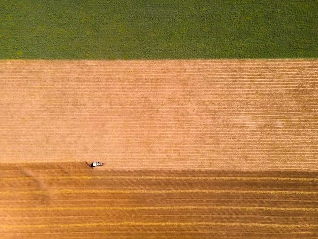 밀의 노란색 필드에 농업 수확기입니다. 다채로운 필드의 공중 무인 항공기 보기입니다. 하향식 보기. 여름철 밀 수확