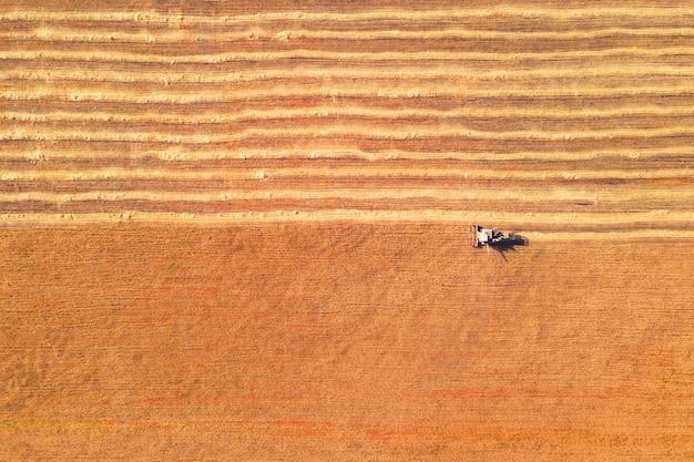 밀의 노란색 필드에 농업 수확기입니다. 다채로운 필드의 공중 하향식 보기입니다. 여름철 밀 수확