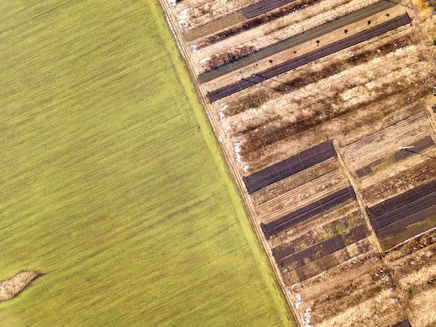 Сельскохозяйственный ландшафт с воздуха. прямая узкая грунтовая дорога между солнечно-зелеными, сухими и коричневыми вспаханными полями.