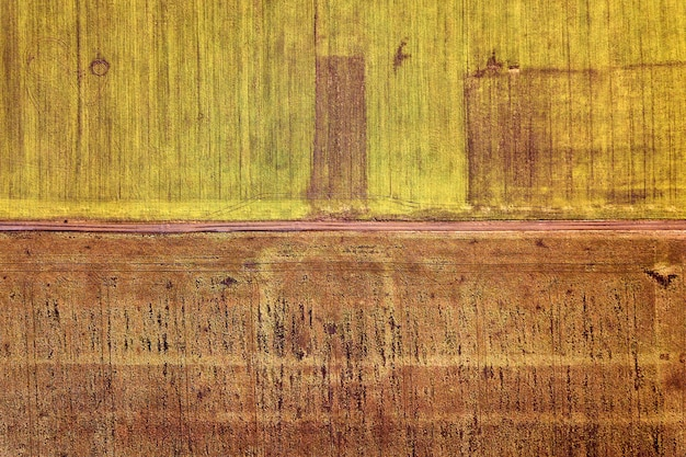 Agricultural landscape from air. straight narrow ground road between sunny green and brown fields background
