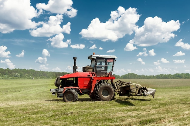Agricultural machinery, harvester mowing grass in a field against a blue sky.