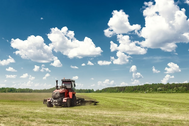 Agricultural machinery, harvester mowing grass in a field against a blue sky