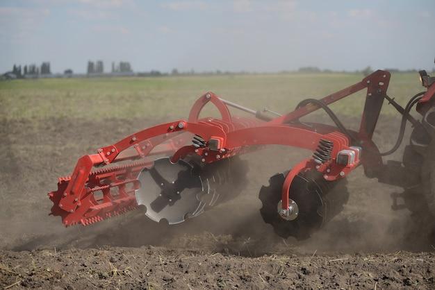 Аграрный плуг крупным планом на земле, сельскохозяйственная техника.