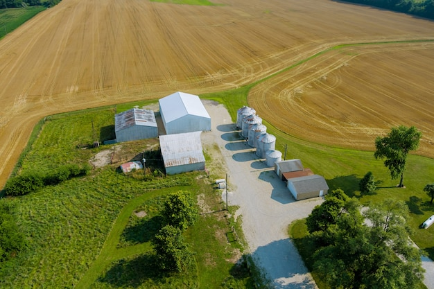 Agricultural products storage with agro elevator on silver silos for processing drying cleaning of aerial panoramic view