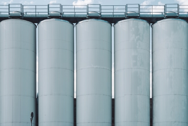 Agricultural silos. storage and drying of grains, wheat, corn, soy, sunflower. industrial building exterior. big metallic silver containers close-up. background of agricultural tanks with copy space.