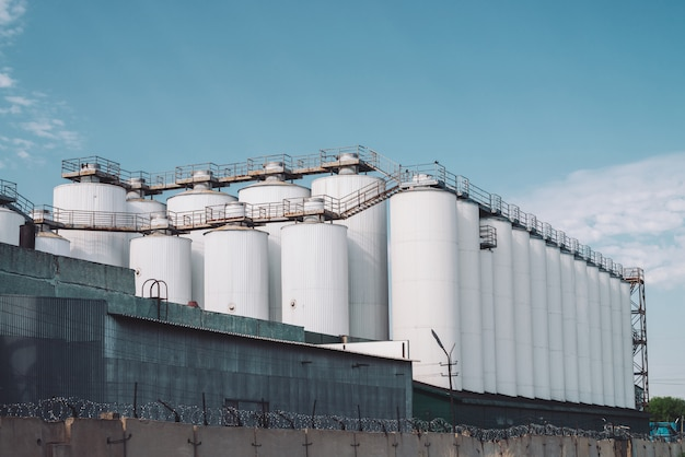 Agricultural silos. storage and drying of grains, wheat, corn, soy, sunflower. industrial building exterior. big metallic silver containers close-up.