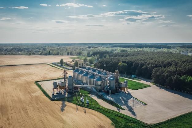 森の近くの農業分野における農業技術。飛行高度からの穀物エレベーターの眺め