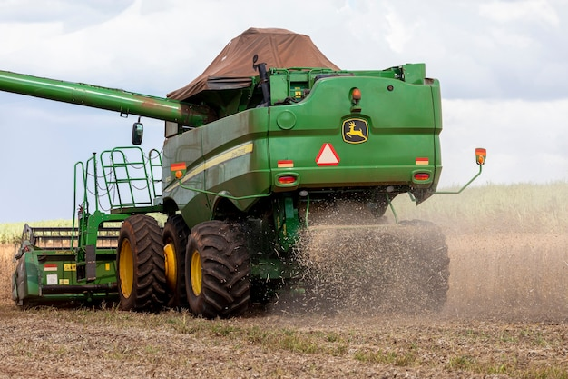 Agricultural tractor harvesting soybeans in the field