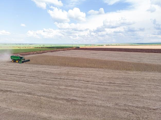 畑で大豆を収穫する農業用トラクター。