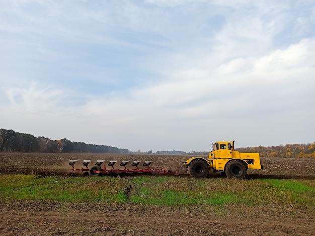 農業用の黄色いトラクターは、フィールドでの乗り物を組み合わせ、地面を処理し、秋にすきが地面を叫びます。