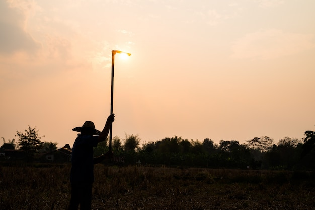 Agriculture farmer life concept: black silhouette of a worker or gardener holding spade is digging soil at sunset light