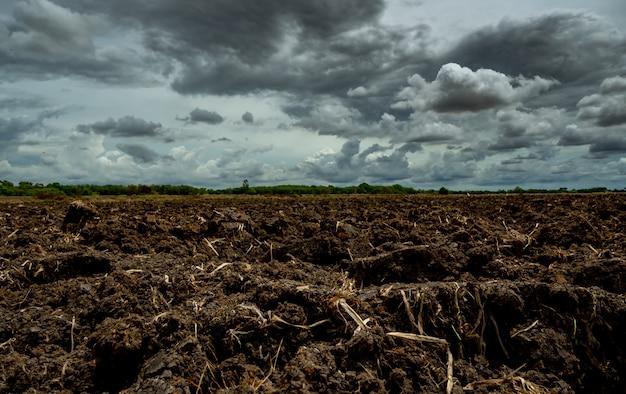 Сельское хозяйство вспаханное поле. черная почва вспахала поле с грозовым небом. грязная почва в ферме. обработка почвы. плодородная почва в органической сельскохозяйственной ферме. пейзаж колхоза.