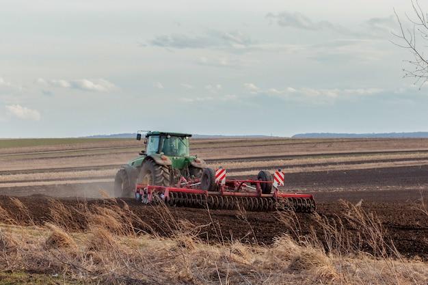農業、農地での農業作業の春先シーズンの前播種活動の一環として苗床耕運機で土地を準備するトラクター