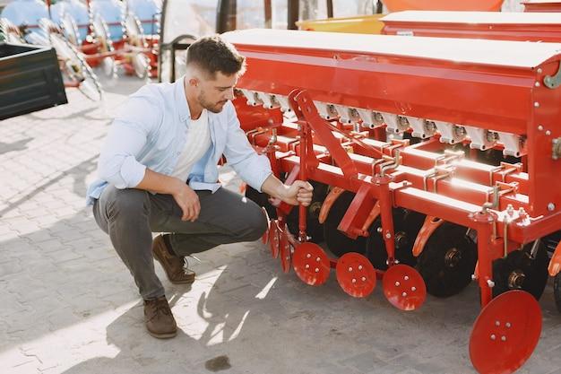 Agronomo che sceglie una nuova fioriera. uomo al suolo all'aperto del negozio. macchinari agricoli.