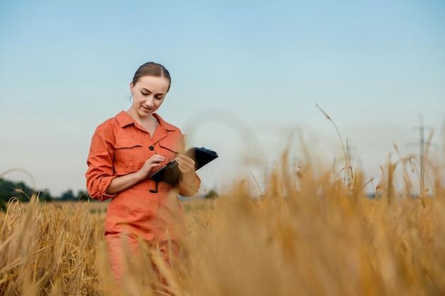 Фермер-агроном с цифровым планшетным компьютером в пшеничном поле с помощью приложений и интернета. умное сельское хозяйство с использованием современных технологий в сельском хозяйстве.