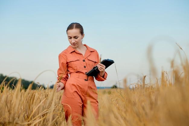 Фермер-агроном с цифровым планшетным компьютером на пшеничном поле с помощью приложений и интернета умное сельское хозяйство