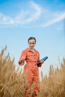 Agronomist farmer with digital tablet computer in wheat field using apps and internet smart farming