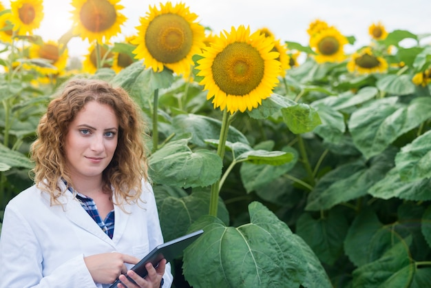Agronomist scientist in white suit holding digital tablet in the field