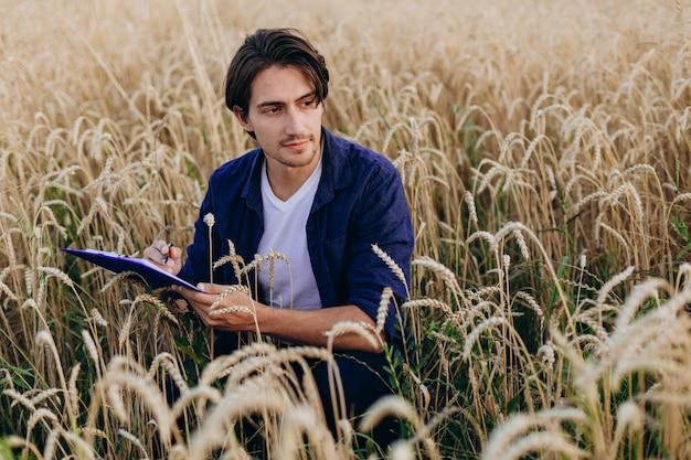 Агроном сидит на пшеничном поле и берет под контроль урожайность.