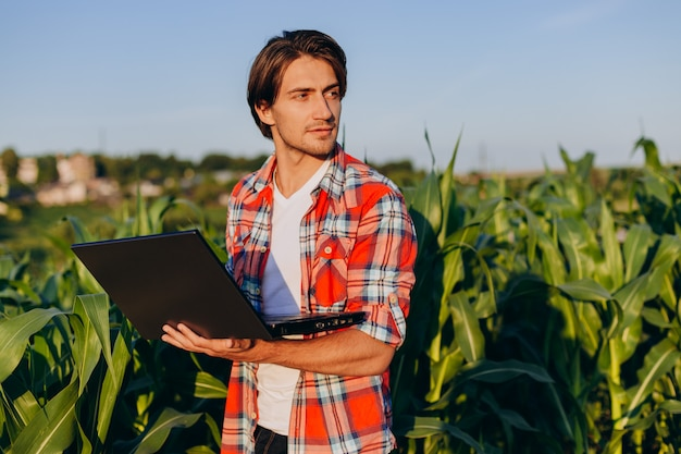 Agronomist standing in a field holding open laptop and smiling and looking out